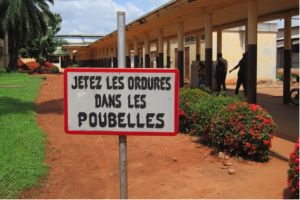 Focused or targeted services only help a few people for a small amount of time. To ensure sustainability, FC+ supports the entire facility by training providers and auxiliary staff to update and maintain infection prevention practices and medical standards. This sign in French is from the grounds of a supported site in DR Congo asking all visitors and staff of the hospital to use trash cans.